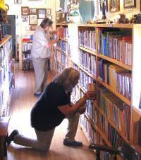 Two unidentified library volunteers are seen here reshelving books. At one point, the library contained in excess of 6,500 books, all received as donations